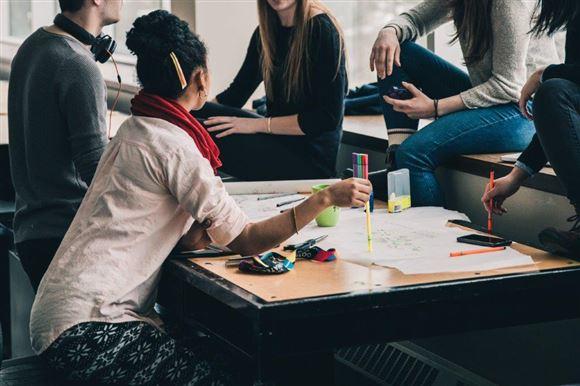 Fem studerende omkring et bord i et studiemiljø
