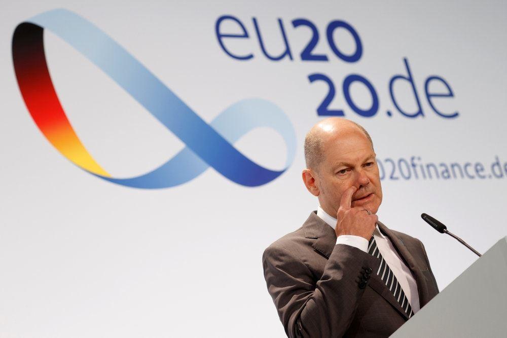Tysklands finansminister, Olaf Scholz på en talerstol med et 20.de skilt bag sig