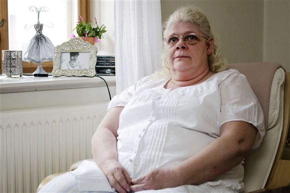 En svær dame i hvidt sidder ved et vindue