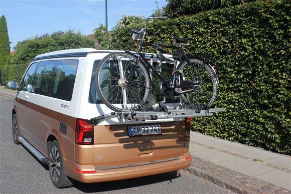 En autocamper bagfra med en cykel på