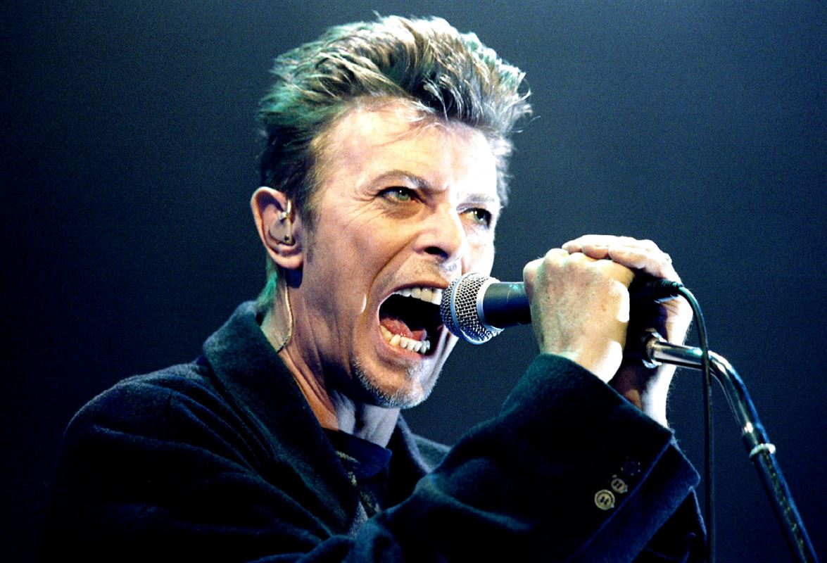Sanger David Bowie på scenen i 1996 mens han synger i en mirkofon.