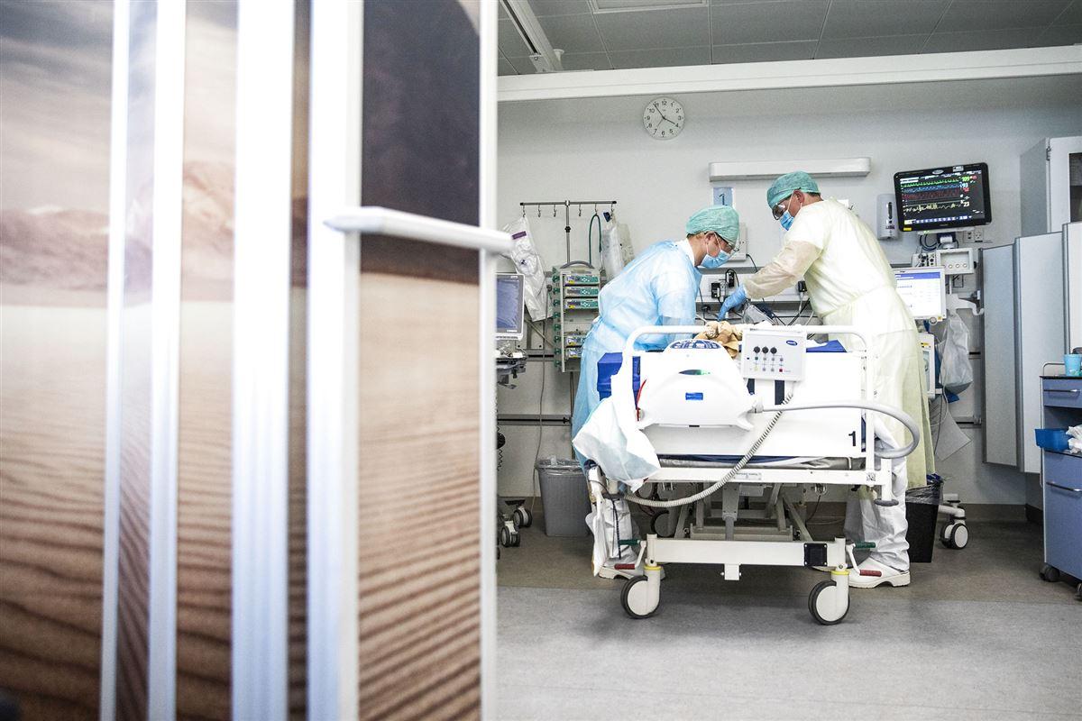 To læger eller sygeplejersker står bøjet over en hospitalsseng. De er iført beskyttelsestøj som kitler, handsker og hårnet.