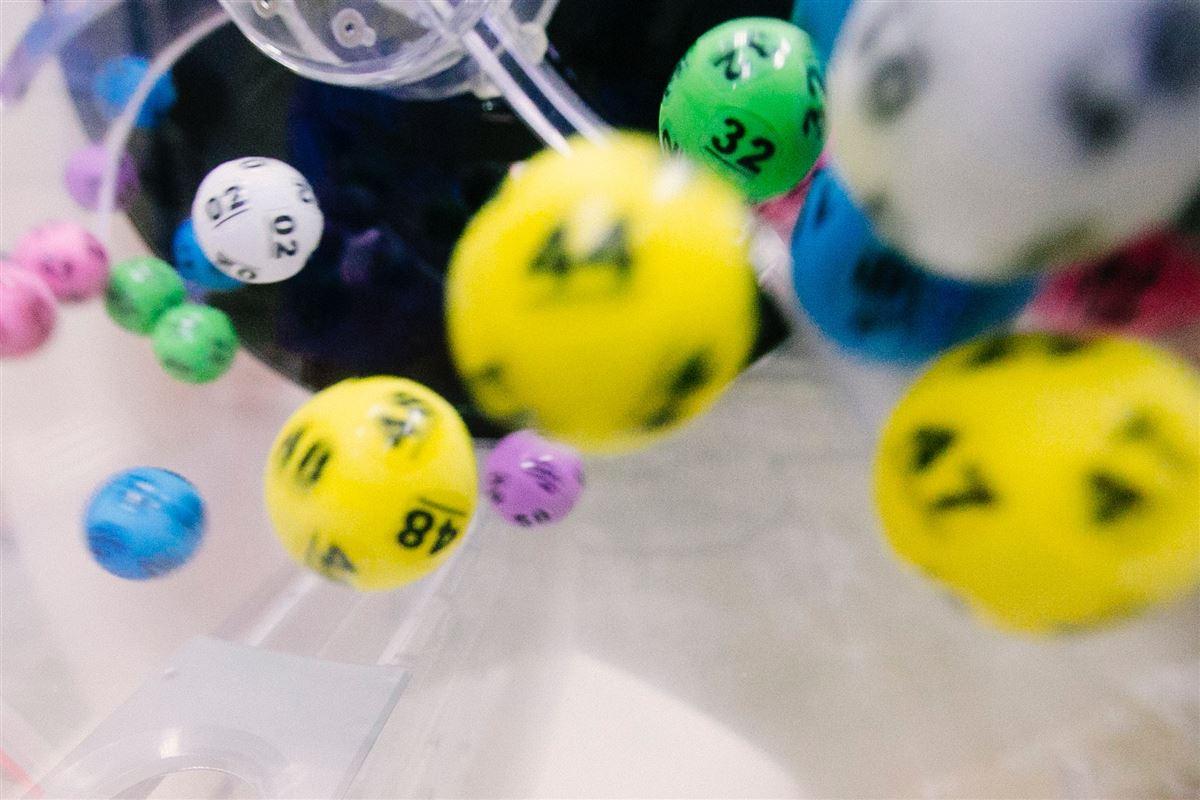 Farvede lottokugler i færd med at blive udtrukket med tallene 44 og 47 mens de andre tal er lidt slørede.