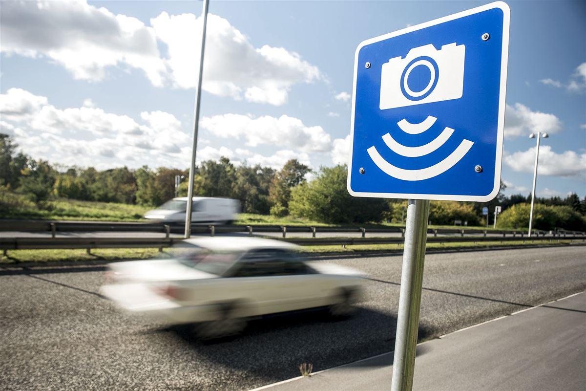 en bil drøner afsted på en vej med et skilt med advarsel om fartkontrol