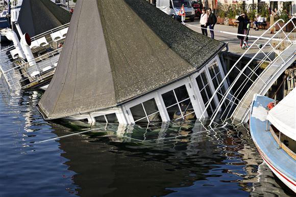 Restaurantskibet Grønsund i Københavns Havn ligger på siden efter at have taget vand ind