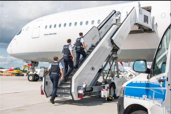 Tre politibetjente på vej ombord på fly