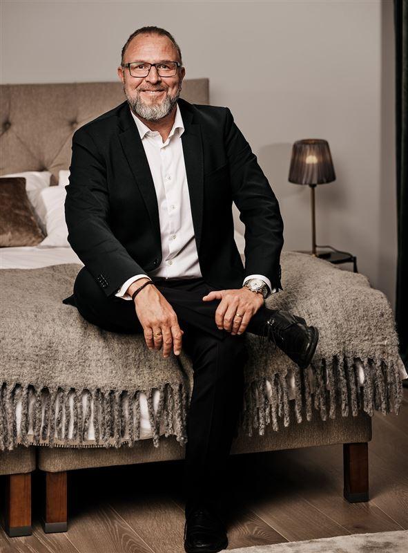 Grundlæggeren af YouBed Matias Sörensen sidder på en seng og smiler