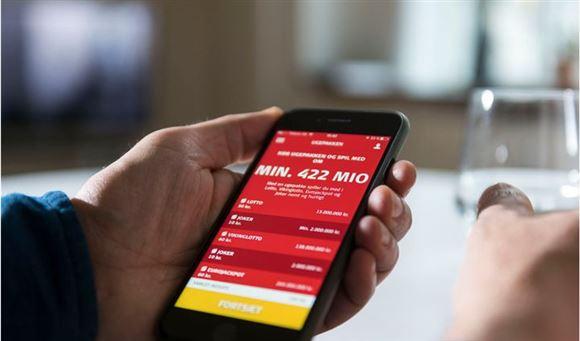 Person holder en mobiltelefon med lotto-app