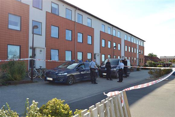 To politibiler holder ude foran en opgang i et mindre socialt boligbyggeri i røde mursten