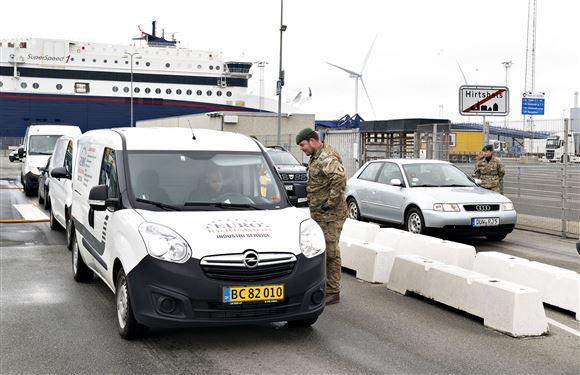 En uniformsklædt mand snakker med en bilist ved færgelejet i Hirtshals.