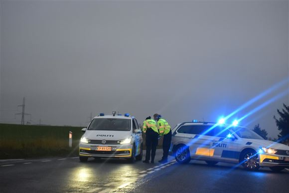 To politibiler med blåt blink spærrer en vej i morgengryen