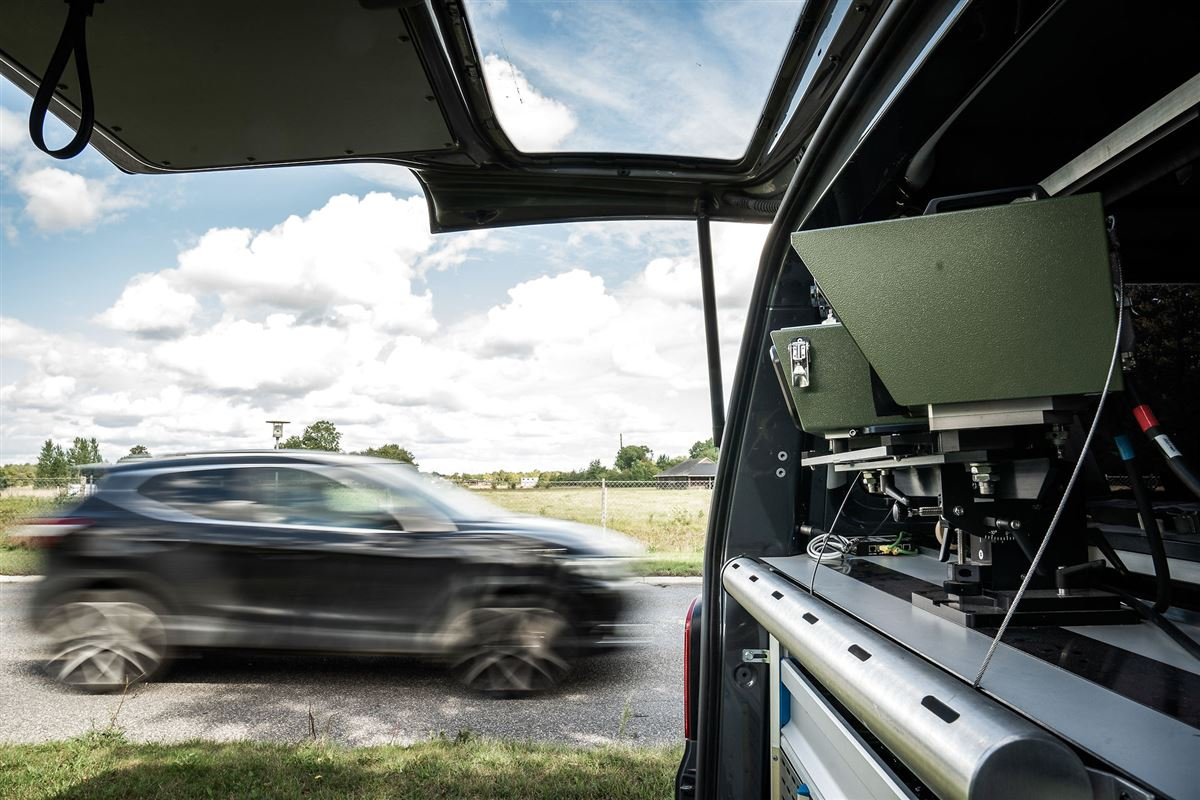 I forgrunden ser man politiets fotovogn med måleudstyr i baggrunden kommer en bil susende.
