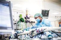 En sygeplejerske med engangskitel, hårnet, mundbind og gummihansker tilser en oatient på intensivafdelingen.