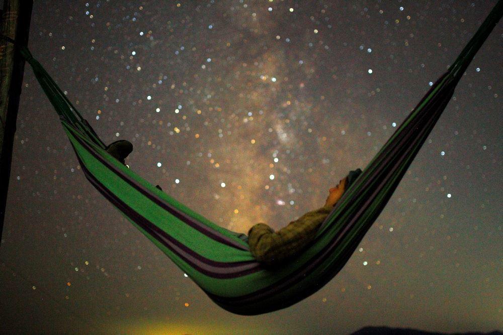 en person ligger i en hængekøje og kigger op på stjernehimmelen