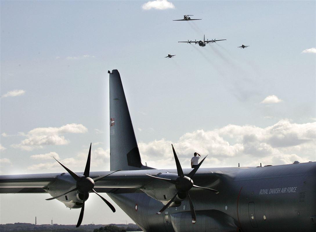 Et stort gråt Herkulesfly holder i en lufthavn. I baggrunden ses flere andre fly i luften.