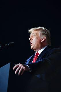 Nærbillede af Donald Trump på en talerstol med et rødt slips og åben mund. Den amerikanske præsident ses i profil.