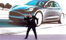 Elon MUsk står foran en Tesla model 3