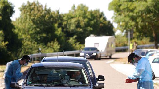 læger tester passagerer i bil for corona