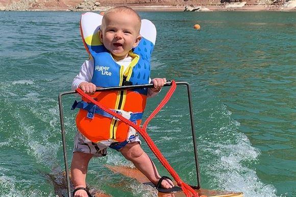 Seks måneder gammel dreng smiler mens han står på vandski