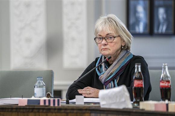 Pia Kjærsgaard fra Dansk Folkeparti sidder ved et bord med en flaske vand og to colaer