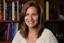 Billede af en smilende dame med bøger i baggrunden