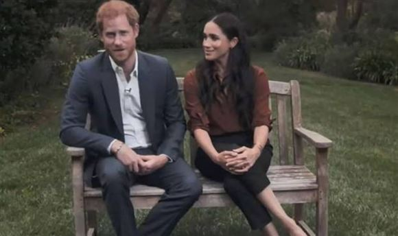 Harry og Meghan sidder på en bænk i en park