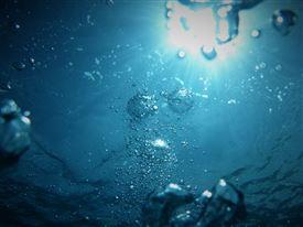 Et blåt univers med bobler og en sol over overfladen