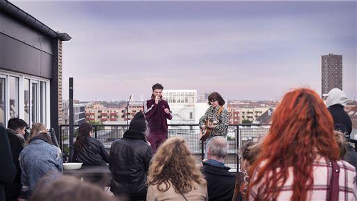 To musikere foran publikummer på en tagtop
