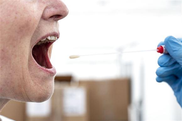 en kvinde bliver testet for corona med en lang vatpind i mundhulen. Vatpinden holdes af en hånd med en blå engangshandske på
