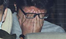 Takahiro Shiraishi skjuler sit ansigt bag sine hænder