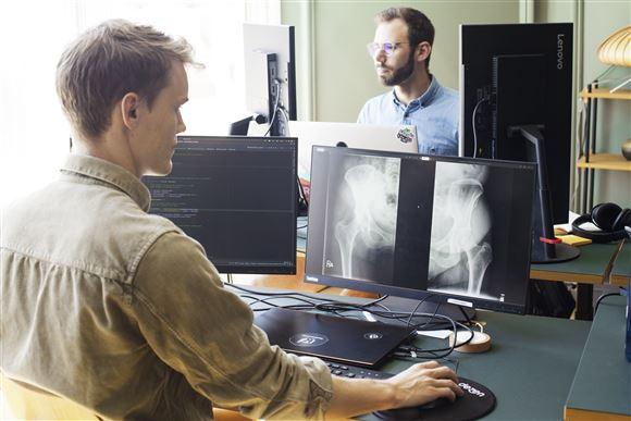 To medarbejdere på et kontor foran deres computerskærme