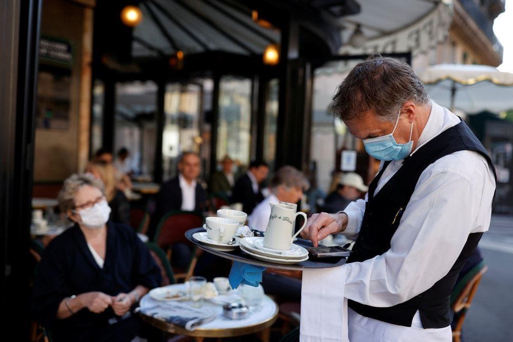 Tjener med mundbind på cafe i Paris