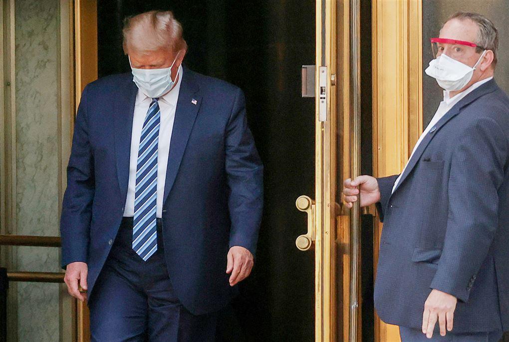 Mand holder dør for Trump iført mundbind.