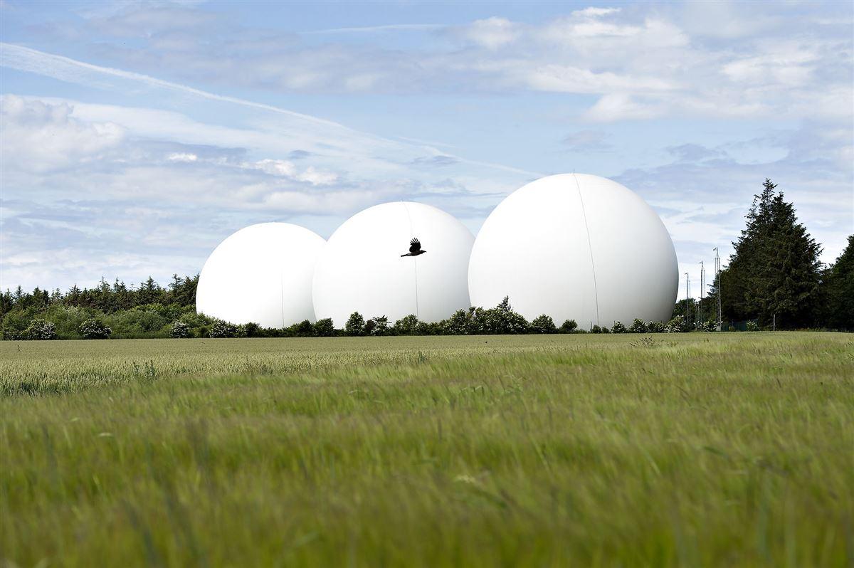 Tre store hvide kugler på en grøn mark, som udgør FET's overvågningsradarer