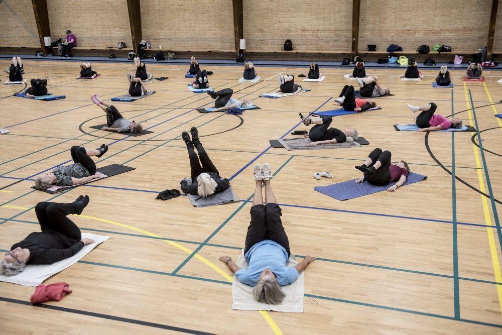 I en gymnastiksal ligger en masse mennesker på tynde madrasser og laver gymnastik