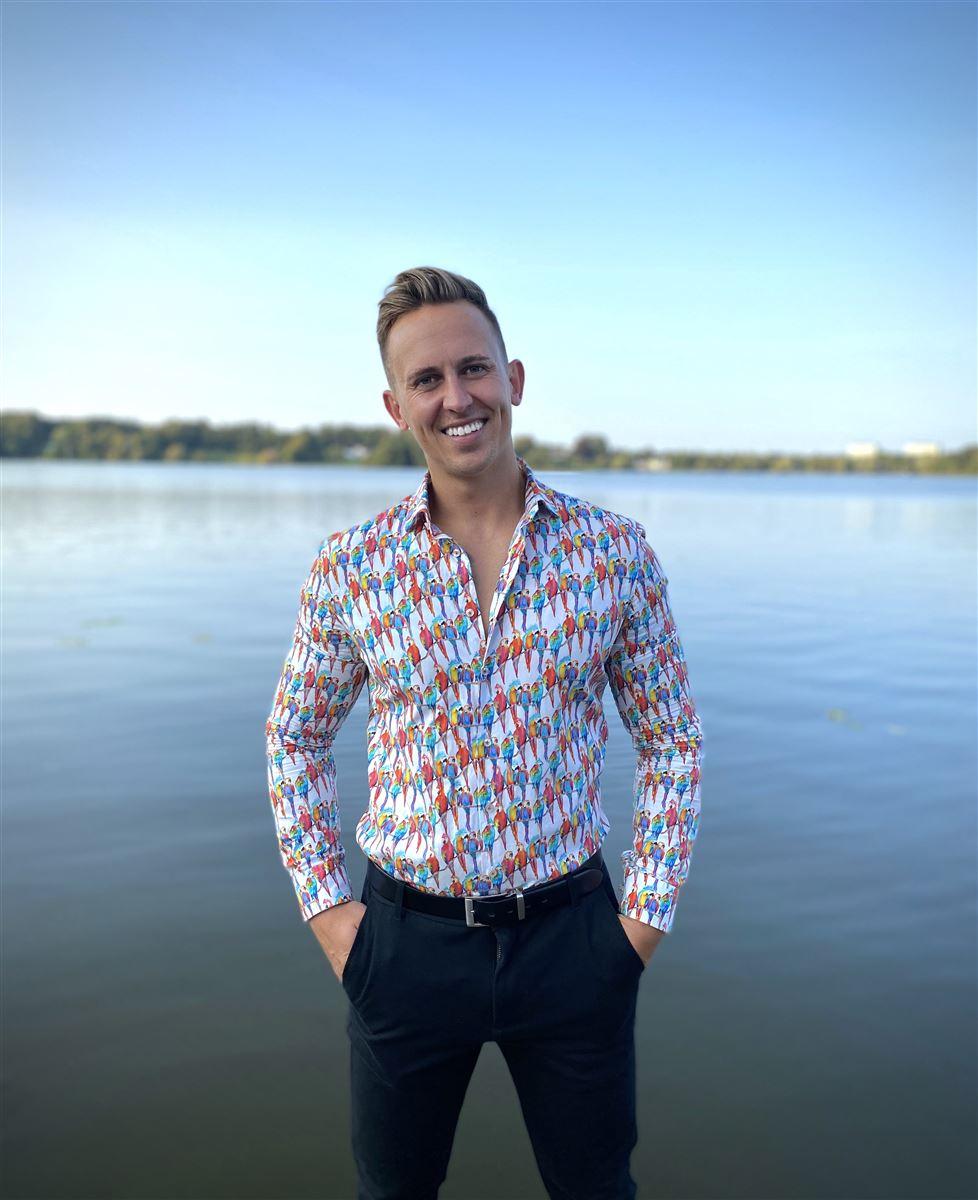 En smilende ung mand i skjorte ved en badebro.
