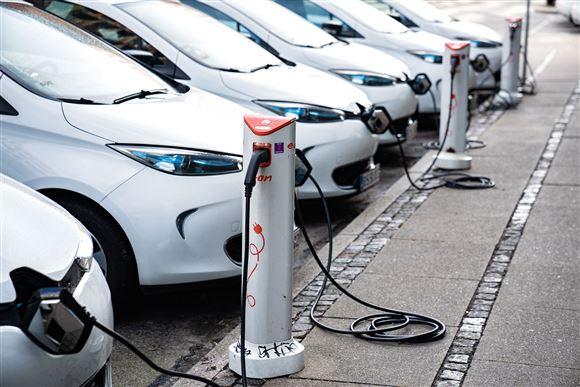 En række elbiler bliver ladet op ved standere