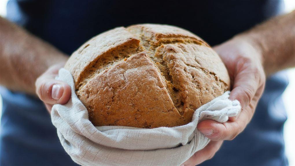 person står med et brød mellem hænderne