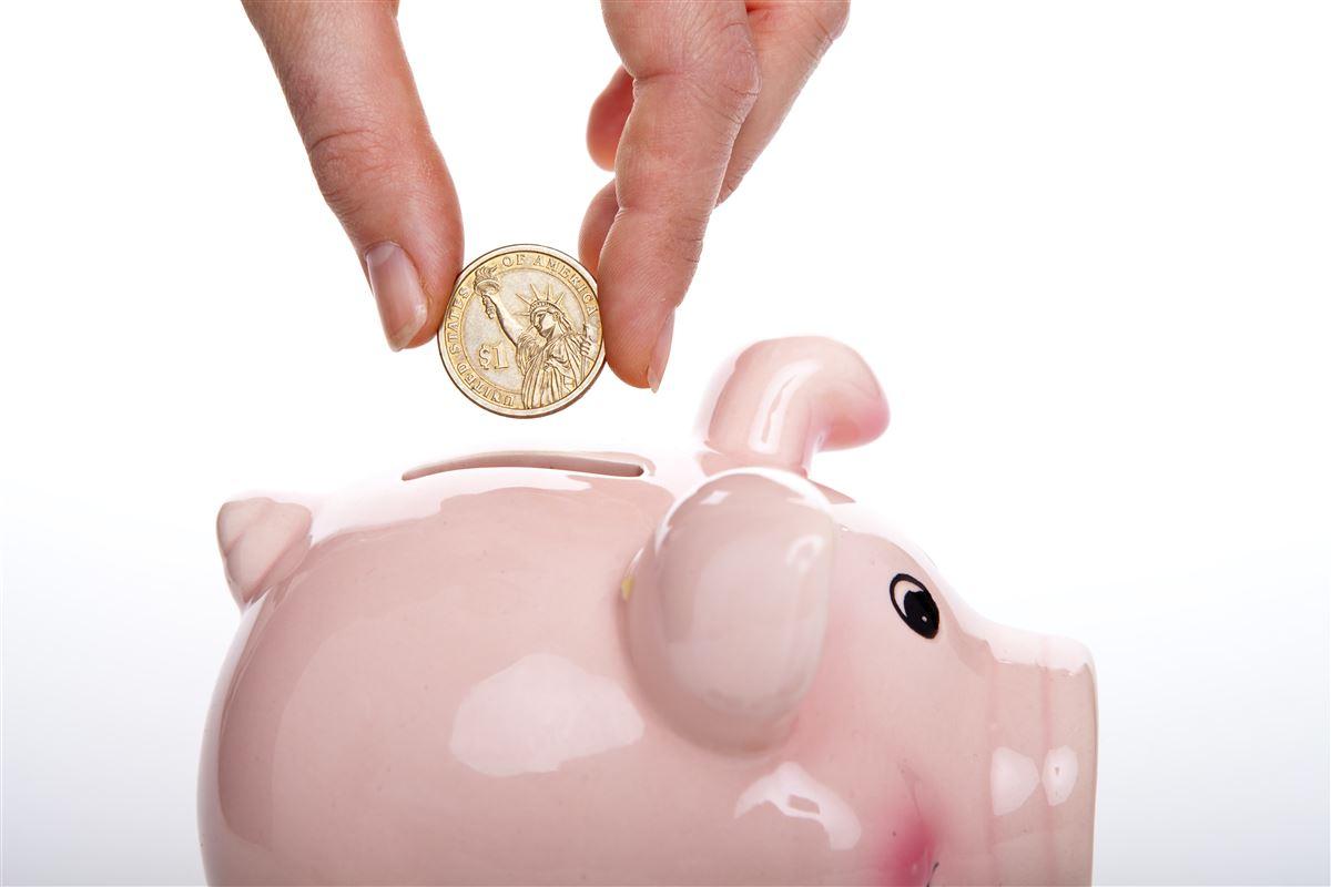 hånd med mønt over sprækken i en sparegris