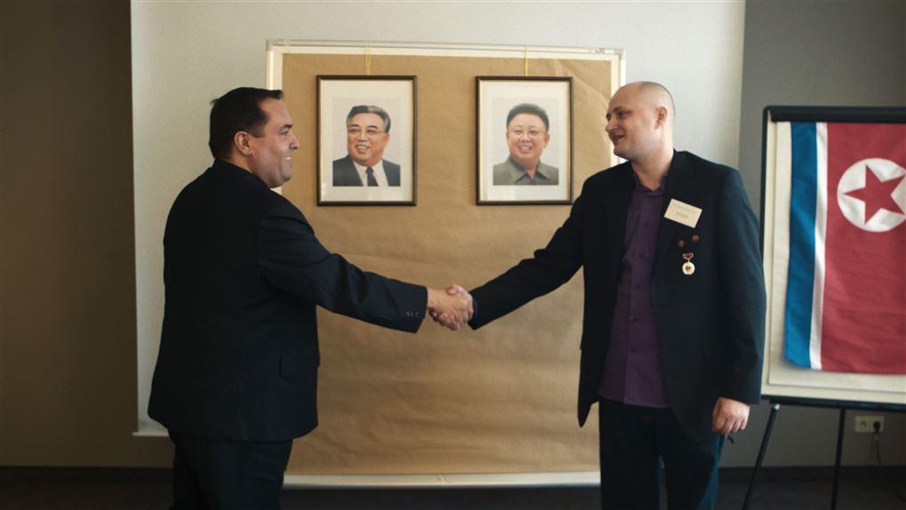 To mænd giver hånd foran billederne af nordkoreanske diktarorer