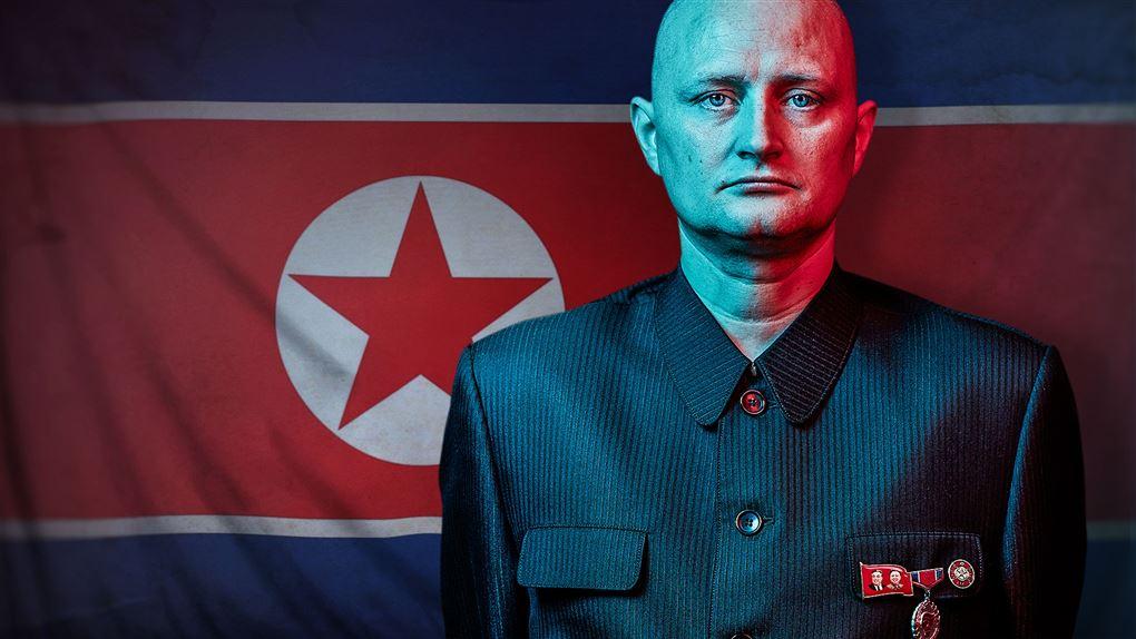 Mand står med sammenbidt udtryk foran det nordkoreanske flag