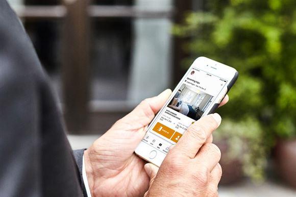 En mand tjekker ind på hotel via mobilen