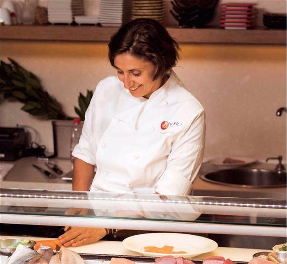 kokken  Eleni Manouso skærer kød bag disk