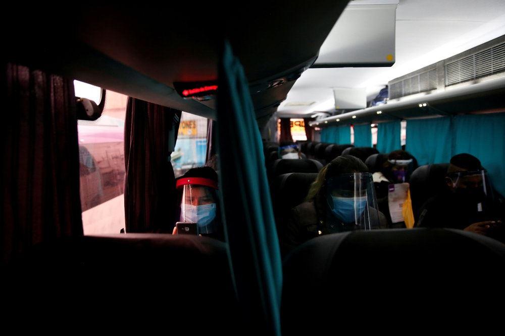 I Peru sidder passagererne i en bus adskilt af gardiner og med hver deres visir og mundbind.