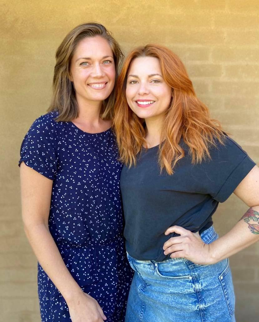 To smukke smilende kvinder - en brunette og en rødhåret.