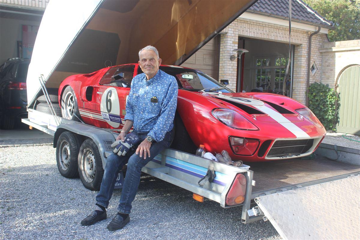 Karsten Ree sidder på en trailer, hvor de står en rød Ford GT40 på.