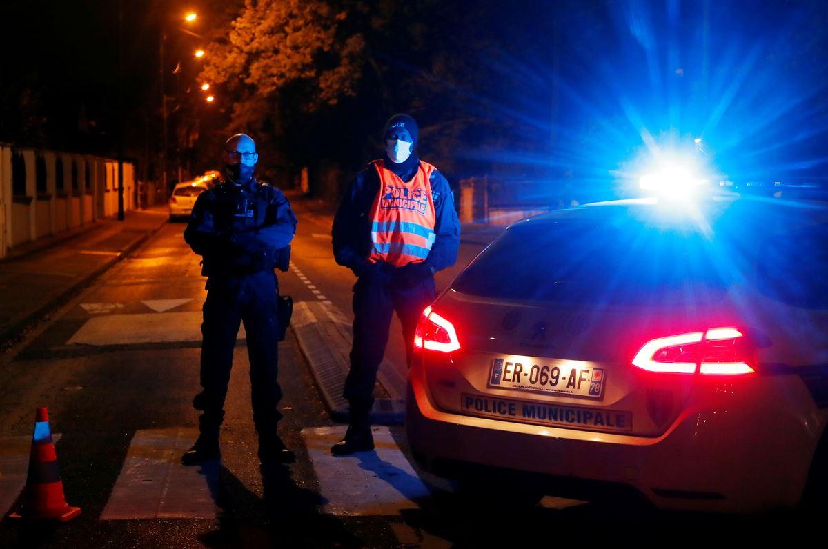 To politifolk og en politibil med udrykning