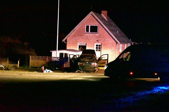 En smadret BMW foran et murstenshus