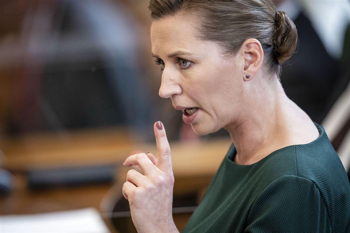 Statsminister Mette Frederiksen med alvorlig mine og en løftet pegefinger hun ses i profil