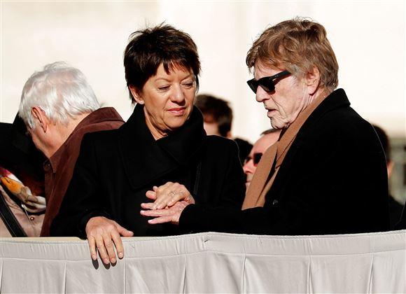 Robert Redford med solbriller i vintersol. Han holder sin kone i hånden. De har begge mørke vinterfrakker på.